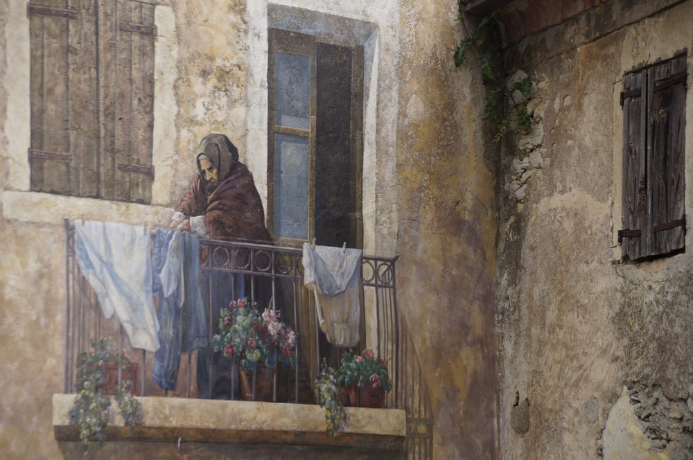 woman on balcony painting