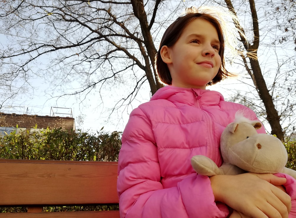 girl sitting on chair pink bubble zip-up jacket while holding hippo plush toy