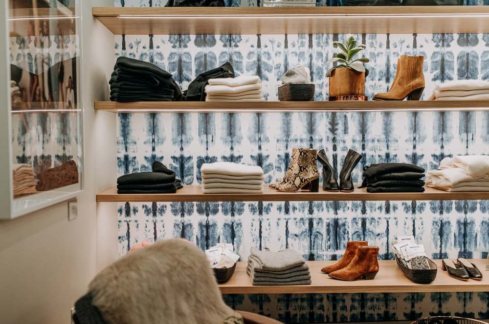 assorted-colored towel near brown leather boots on brown wooden shelf