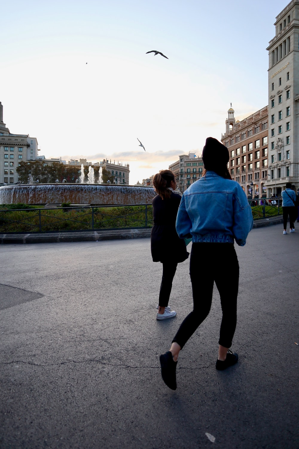 people walking near fountain and buildings during day