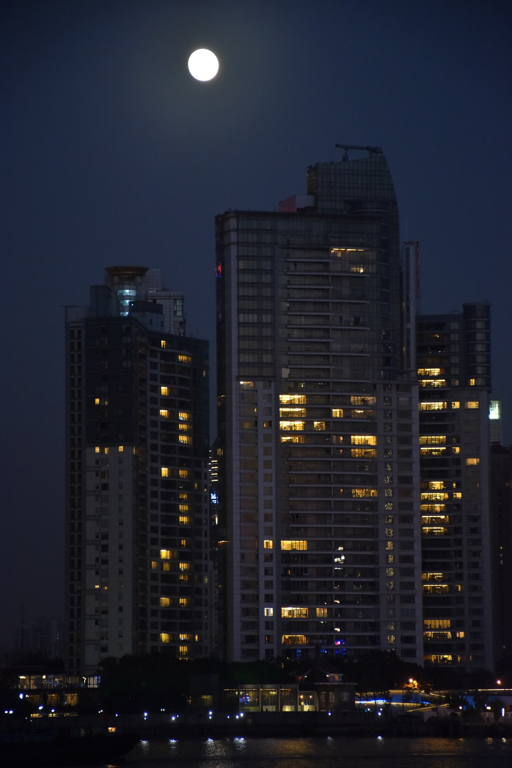 view photography of high rise buildings during nighttime with full moon