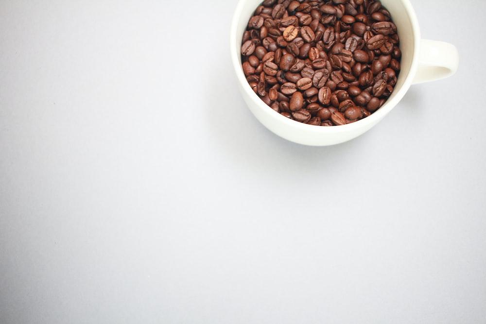 brown coffee beans in white ceramic mug