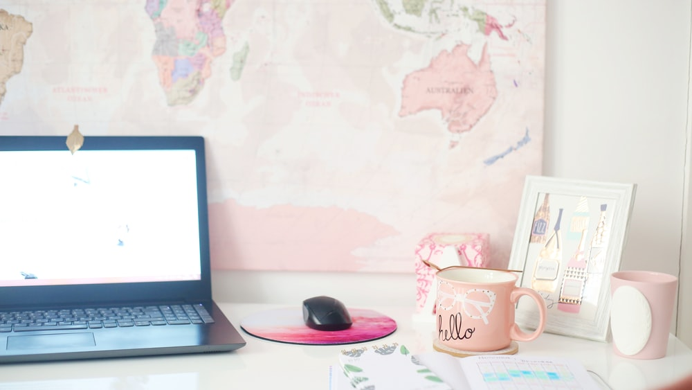 desk with turned-on laptop, mouse, mousepad and cup of coffee