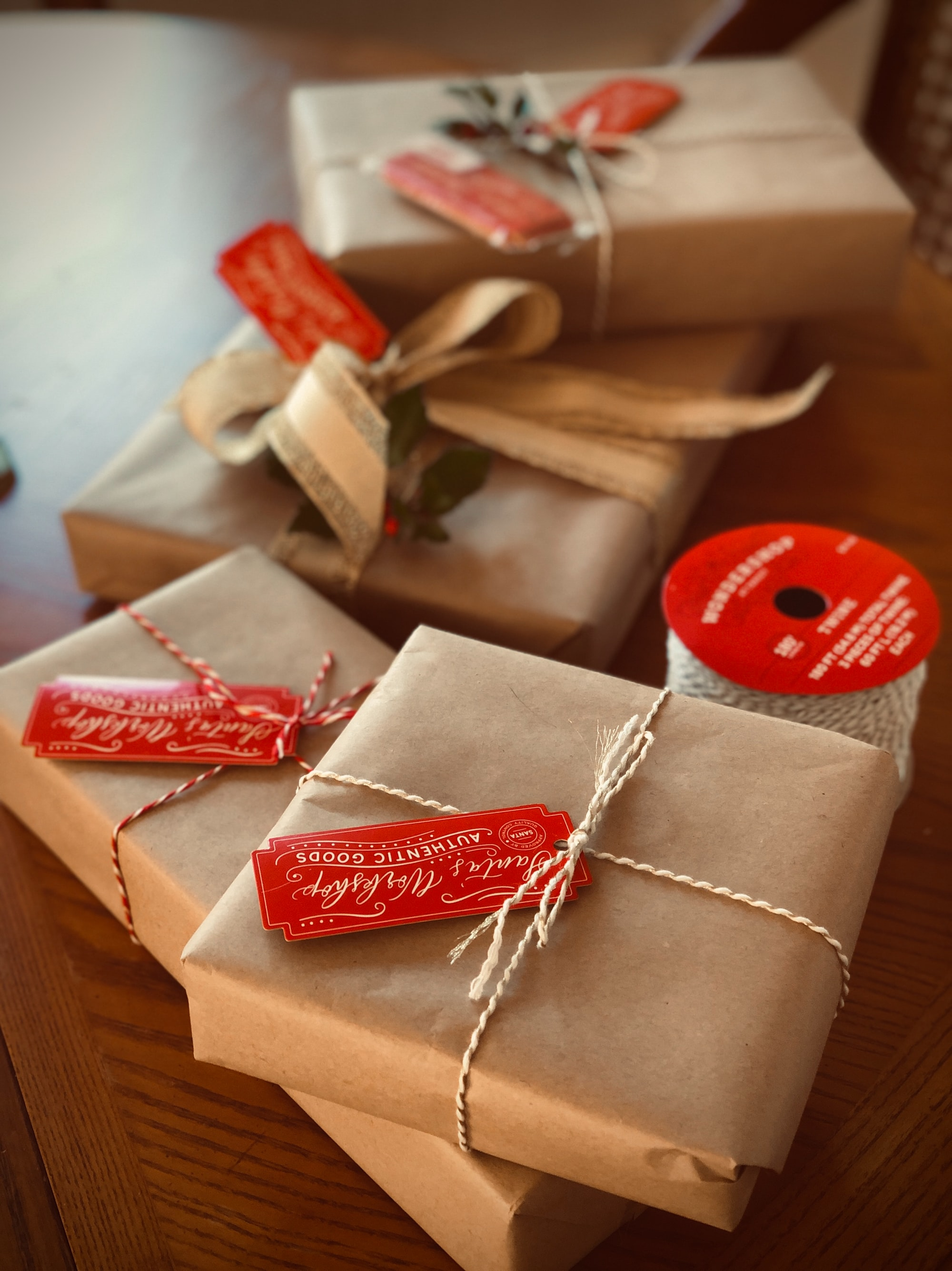 Christmas presents wrapped in plain brown paper with white and gold twine and cute Santa's Workshop gift tag attached. There are also some twigs of holly added to the presents for a little extra appeal!