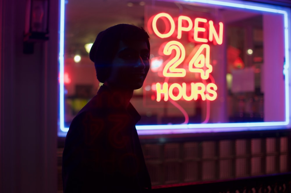 man standing beside open 24 hours signage during nighttime