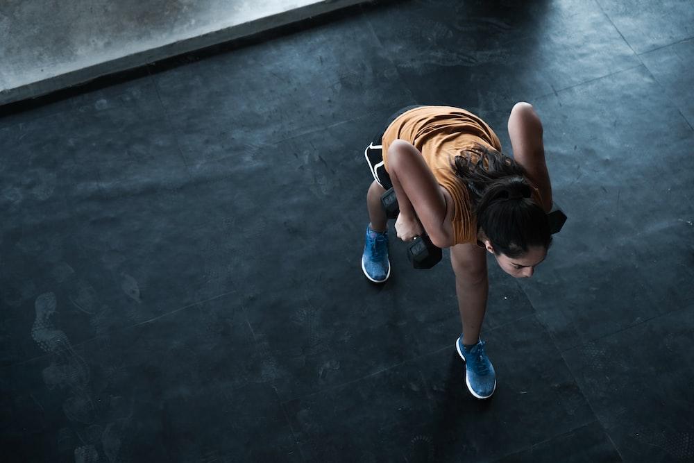 woman in orange top exercising indoors
