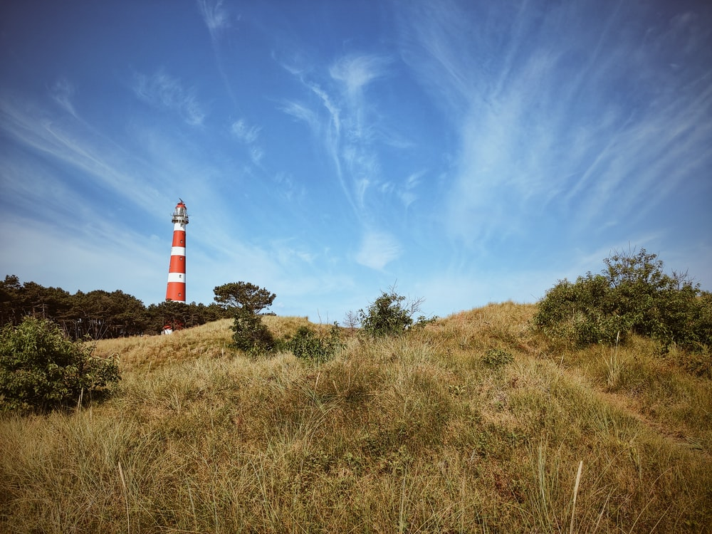 lighthouse on top of a mountain under a calm blue sky
