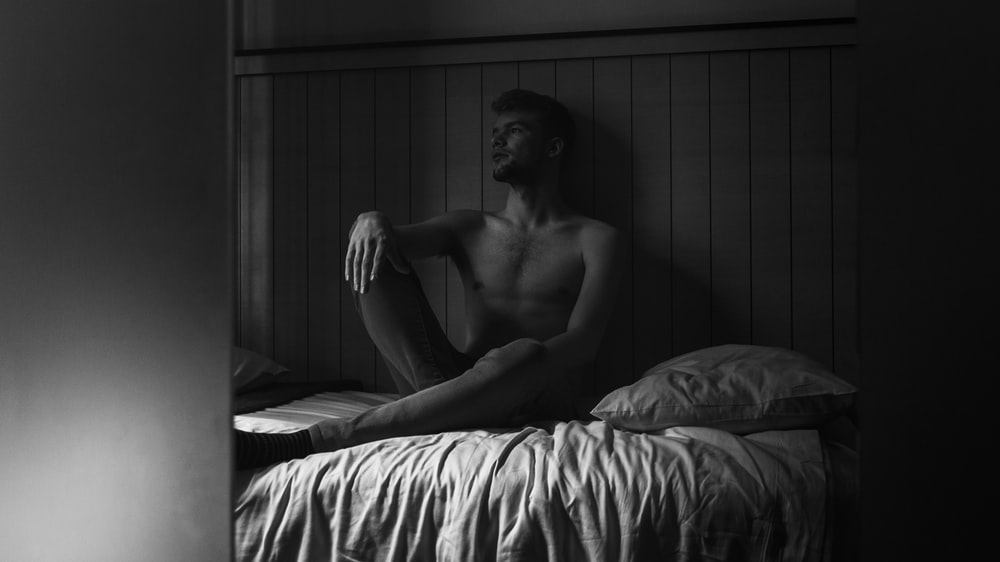 greyscale photography of man sitting on bed