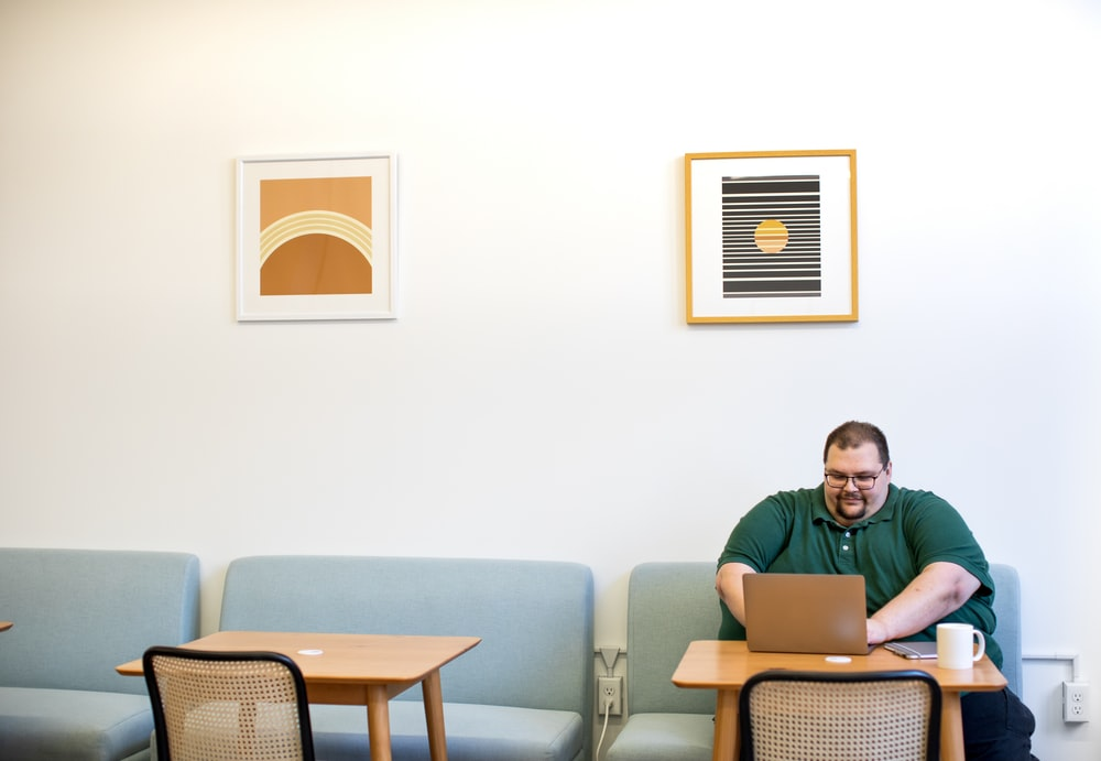 man in green polo shirt sitting on sofa near table while using laptop computer inside room