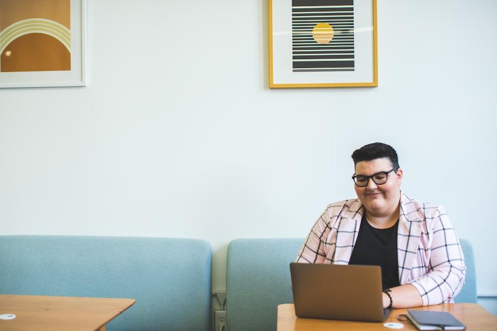 smiling man sitting on chair using laptop
