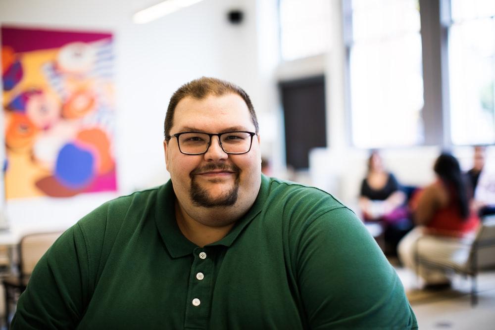 smiling man in green polo shirt wearing eyeglasses