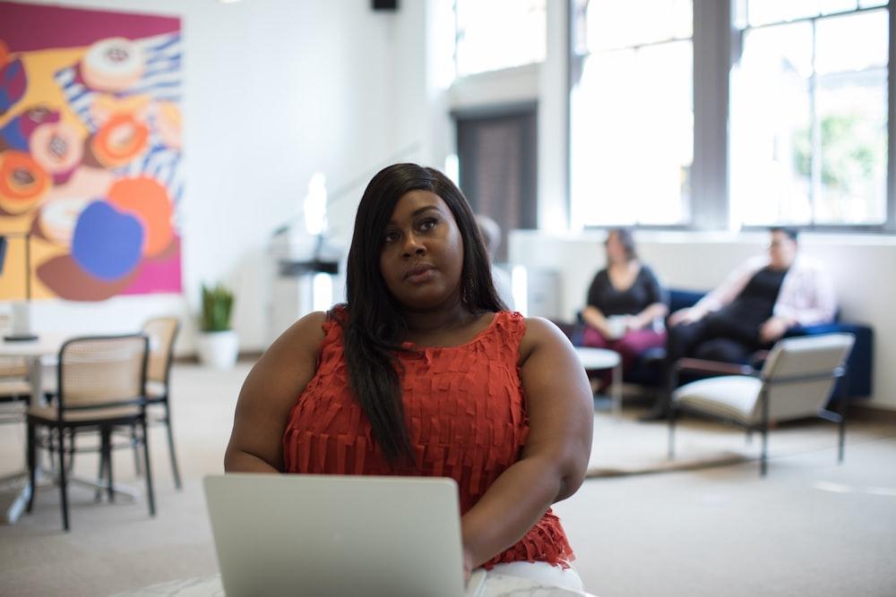 woman in orange sleeveless top using laptop computer inside building