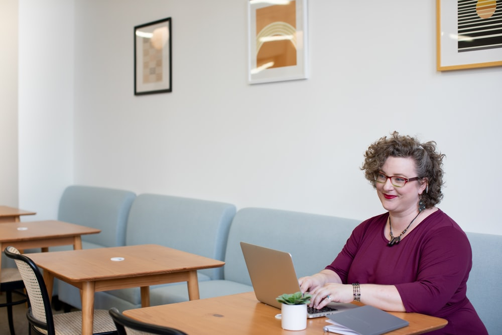 smirking woman using laptop computer