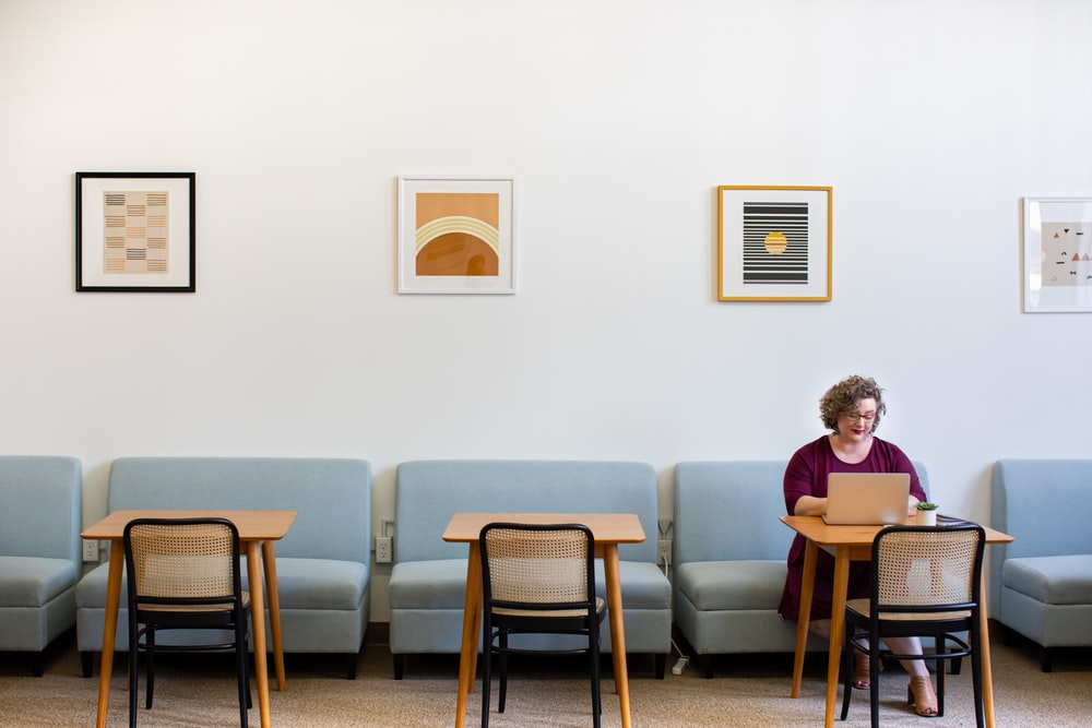 woman sitting on sofa near tables inside room