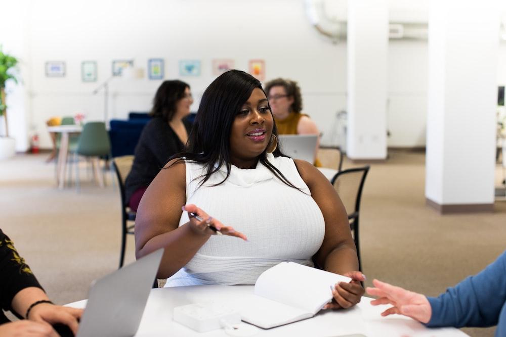 shallow focus photo of woman in white sleeveless shirt