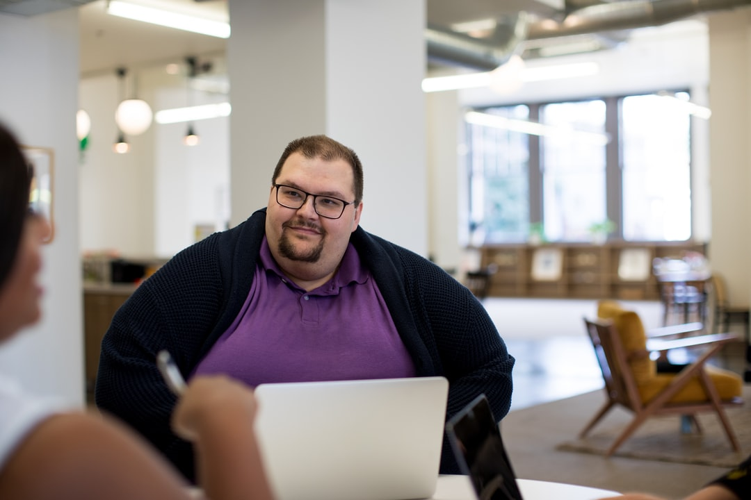 Big and tall man working in a bright, open, modern office on a computer