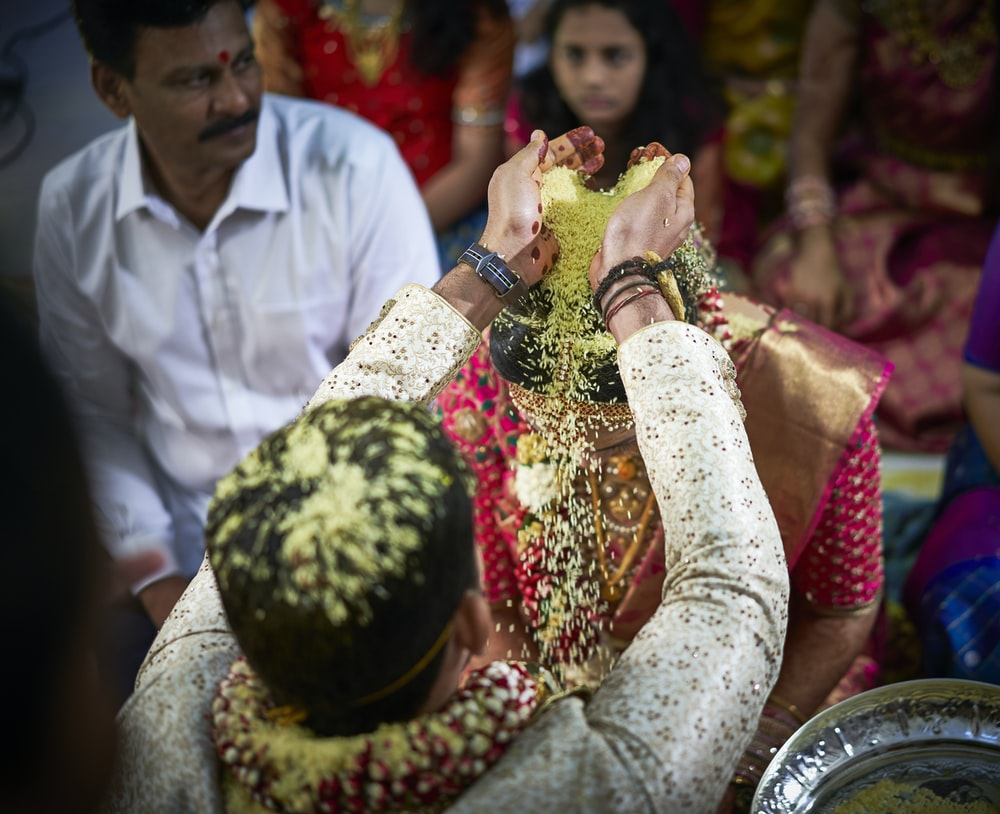 man standing while pouring substance on head of woman in wedding ceremony
