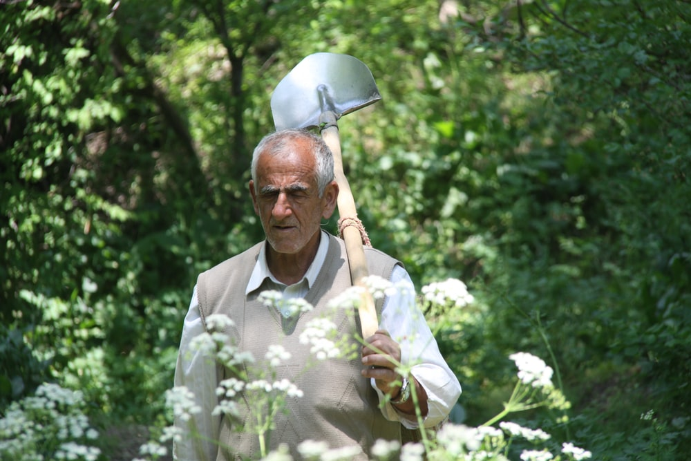 man with shovel in forest