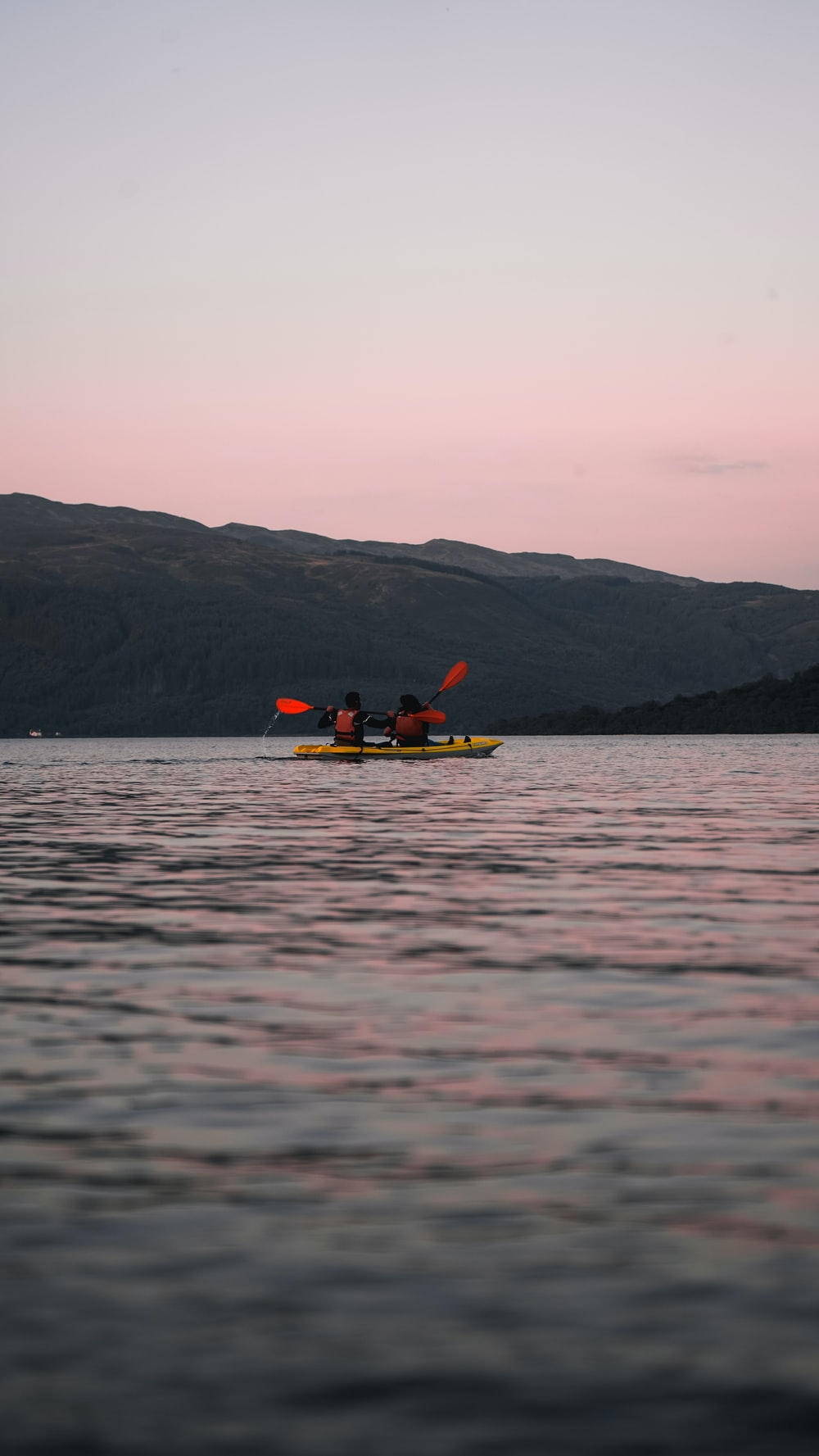 photography of two person riding kayak during daytime
