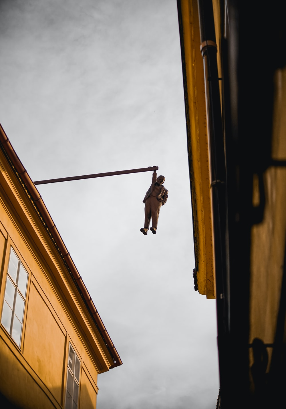 low-angle photography of statue of person hanging on rail during daytime