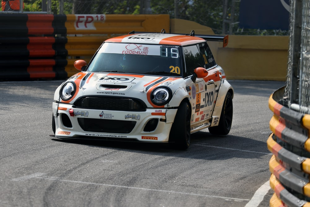 white and orange race car on a race track
