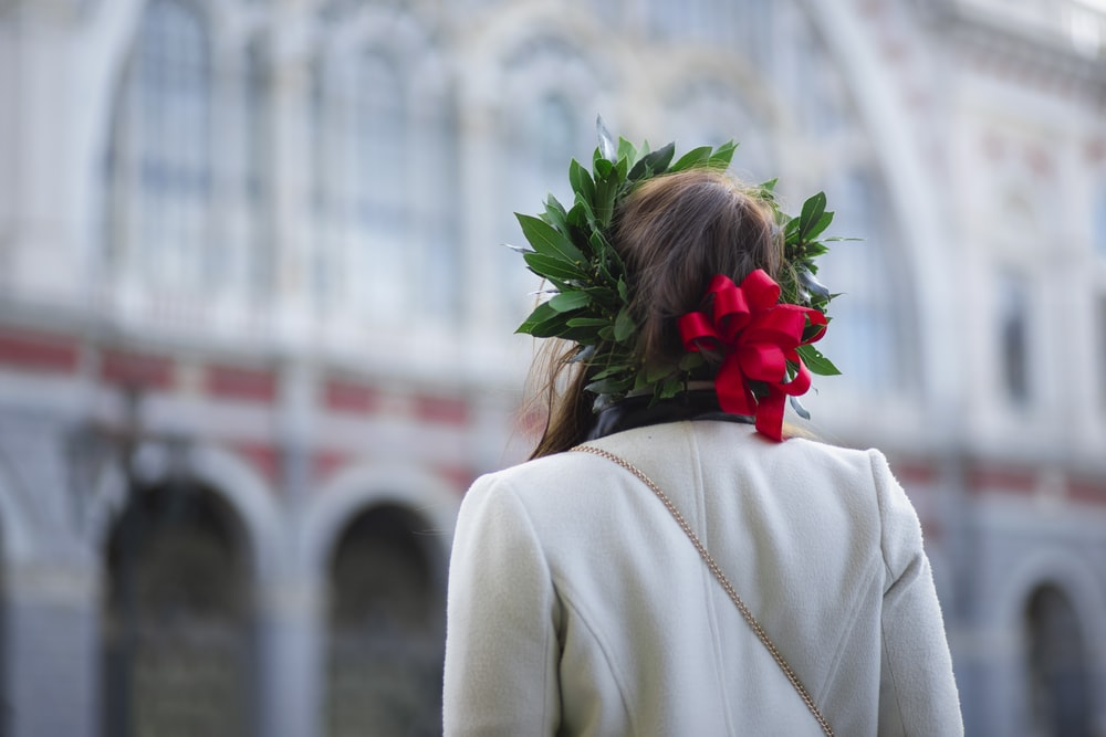 woman facing to a building wearing a floral headpiece