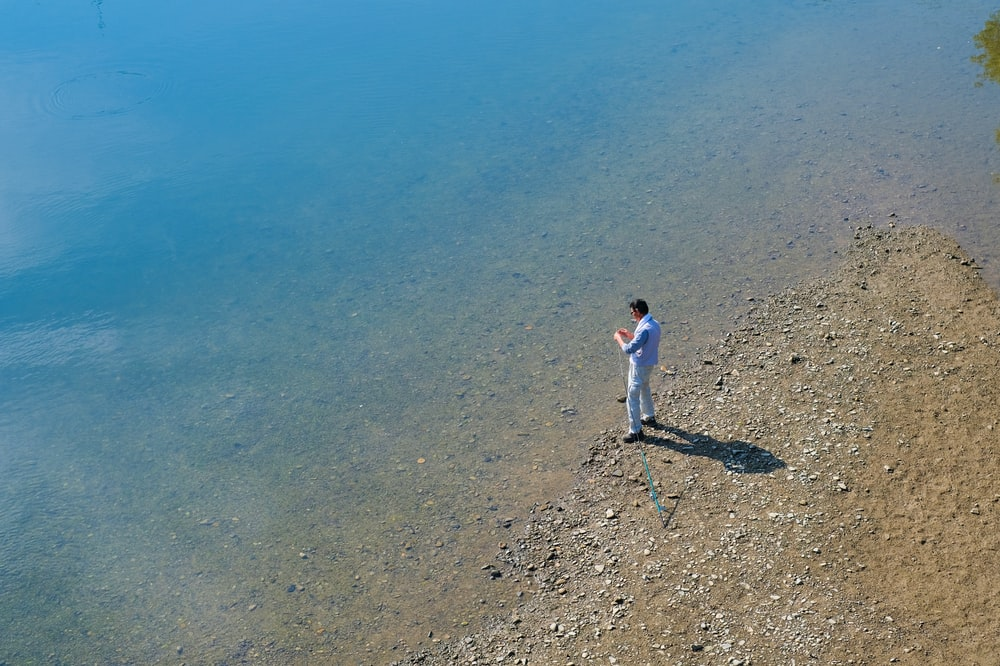 man standing on seashore during daytime