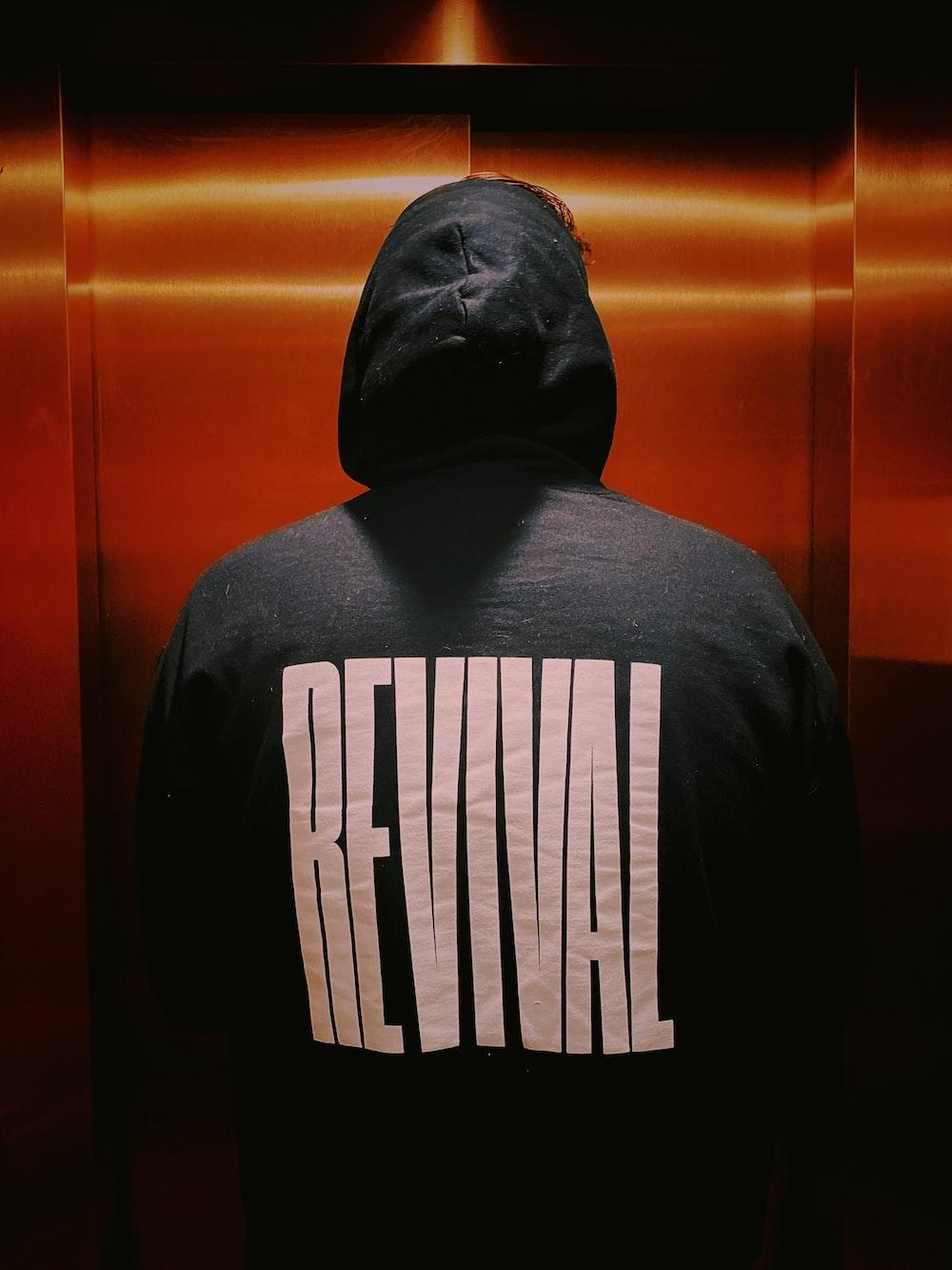 person wearing black Revival hoodie jacket