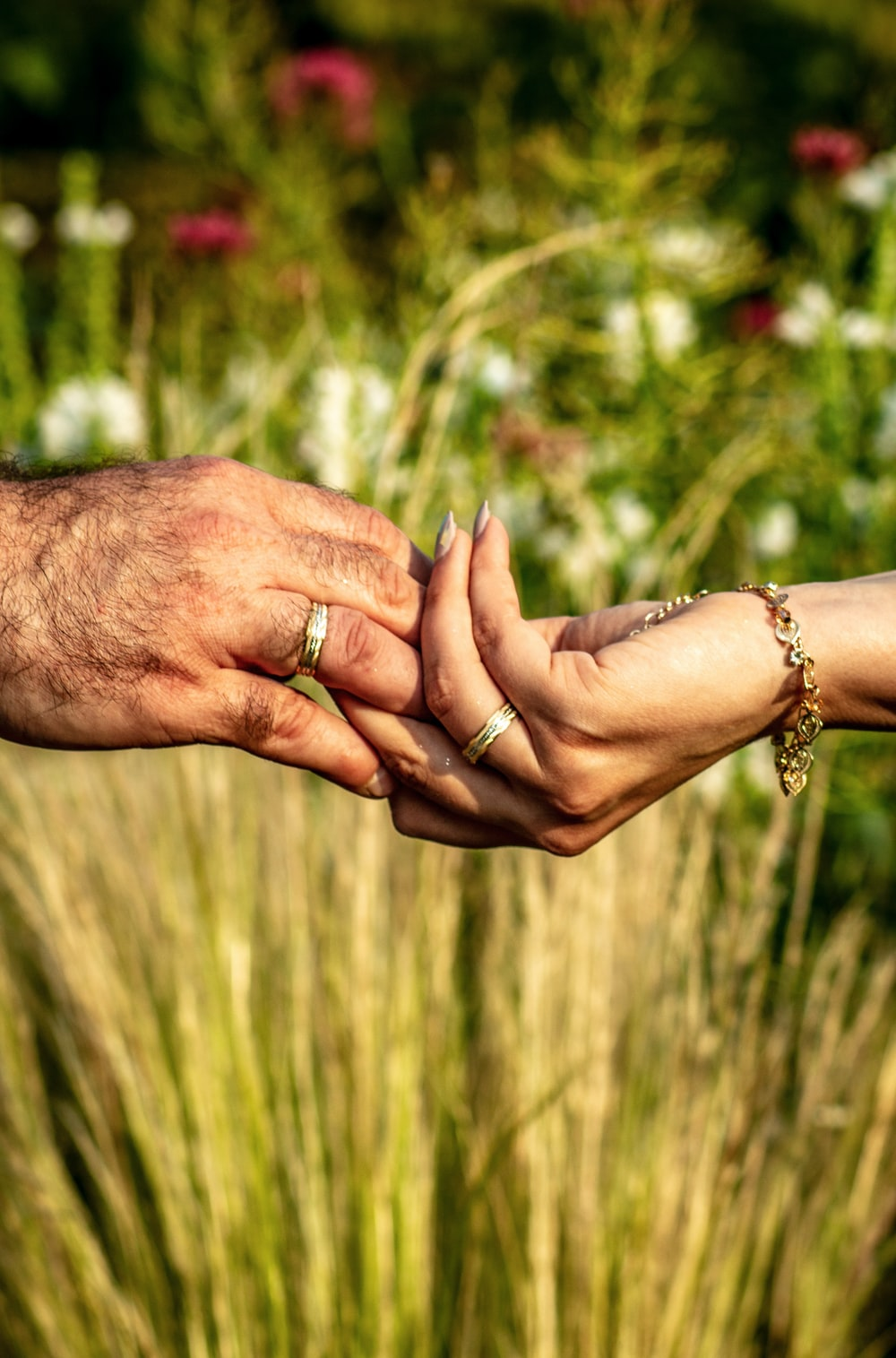 holdings hands with gold-colored ring over flower garden