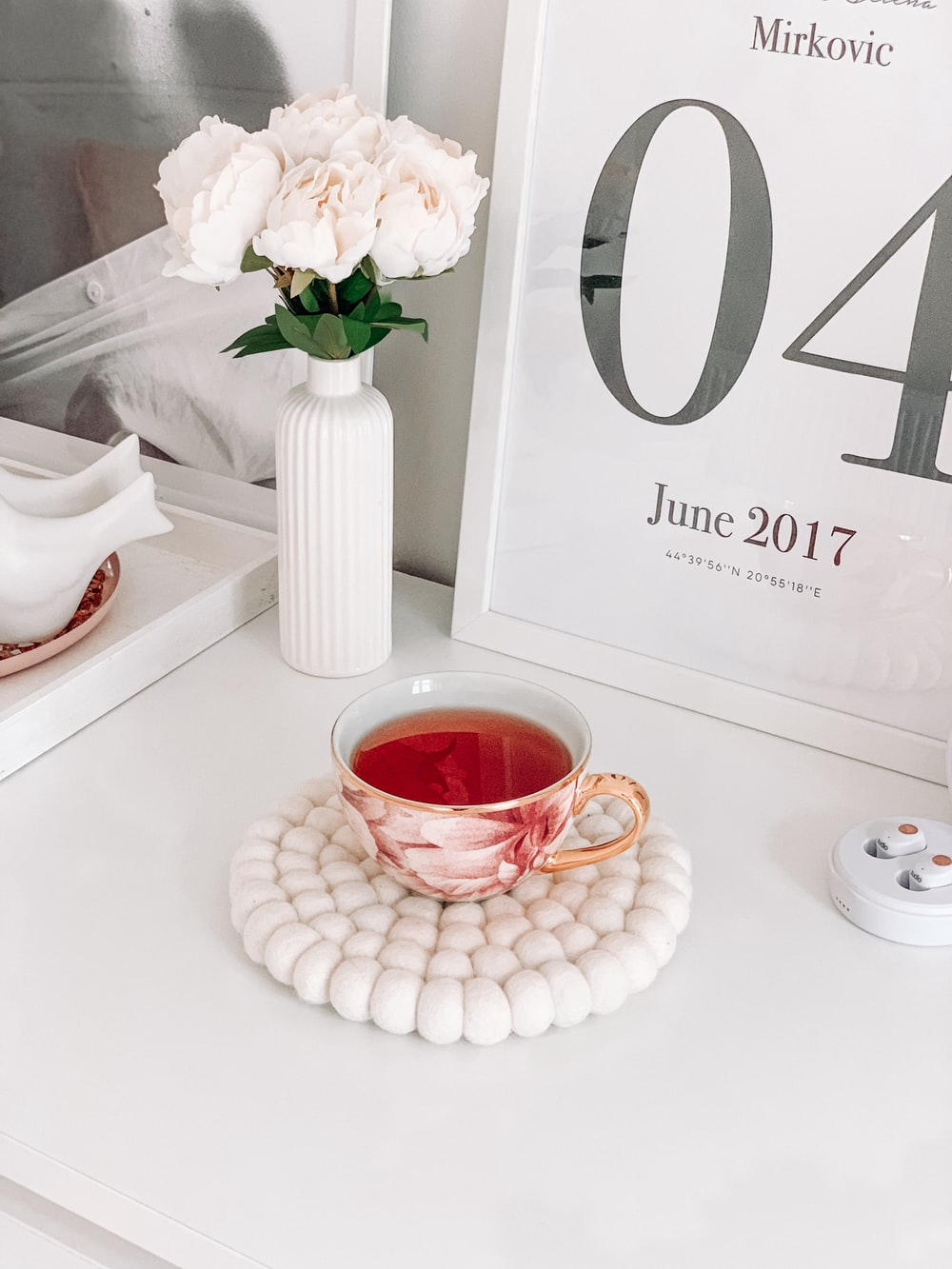 red and white ceramic teacup filled with red liquid