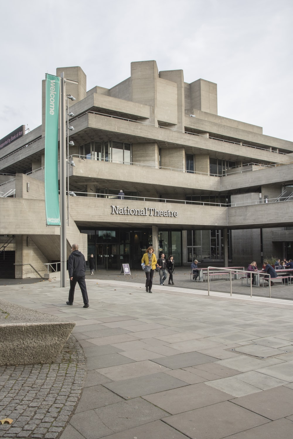 people walking in front of National Theatre building