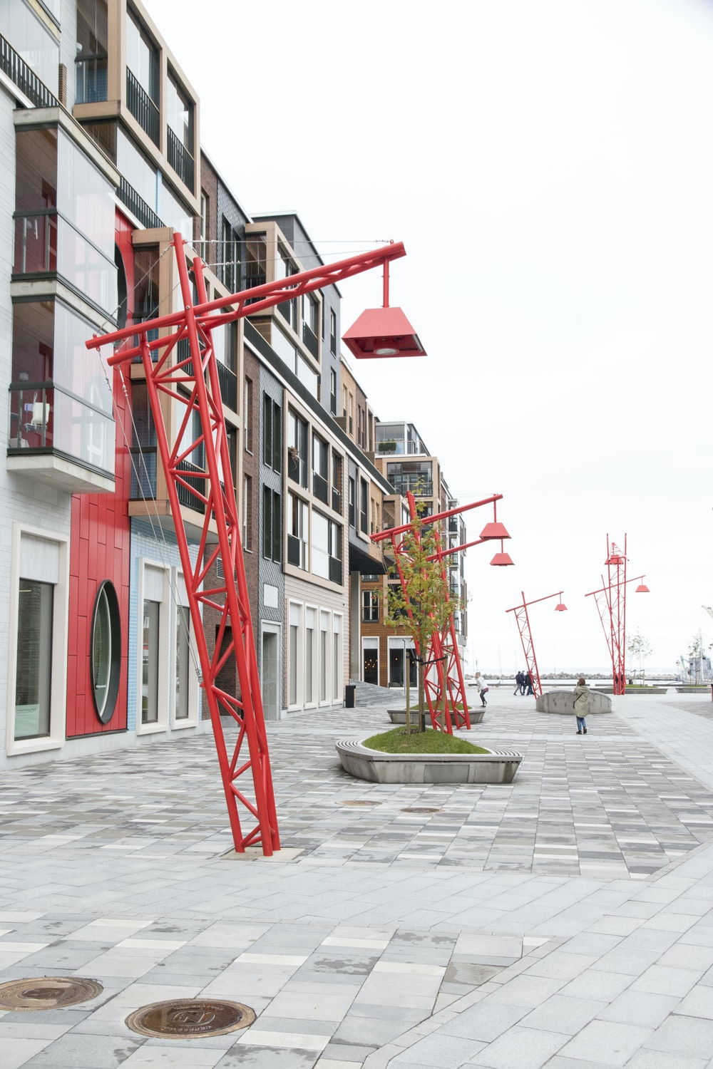 red concrete outdoor lamp post near clear glass walled building