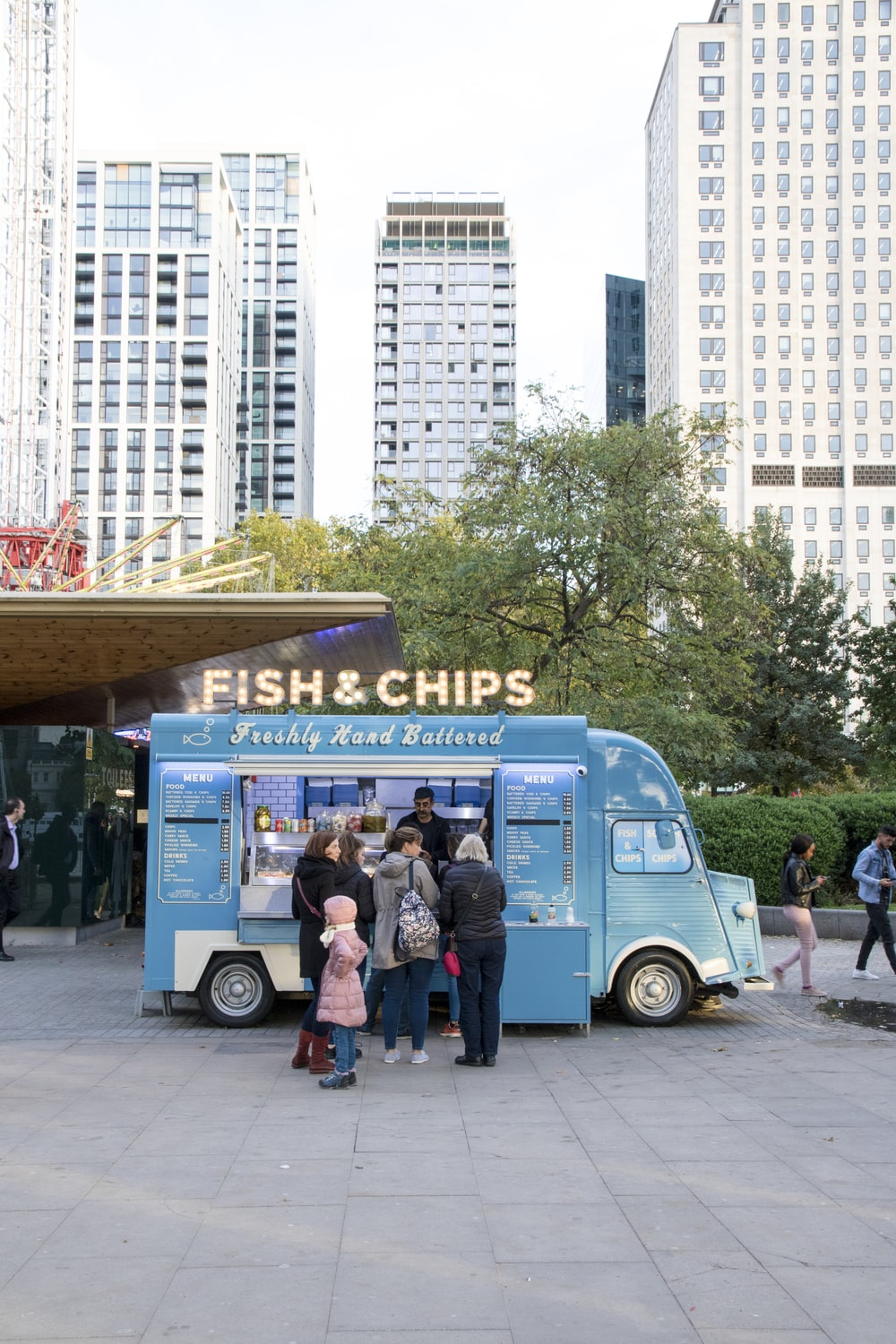 people beside Fish & Chips food truck at the city during day