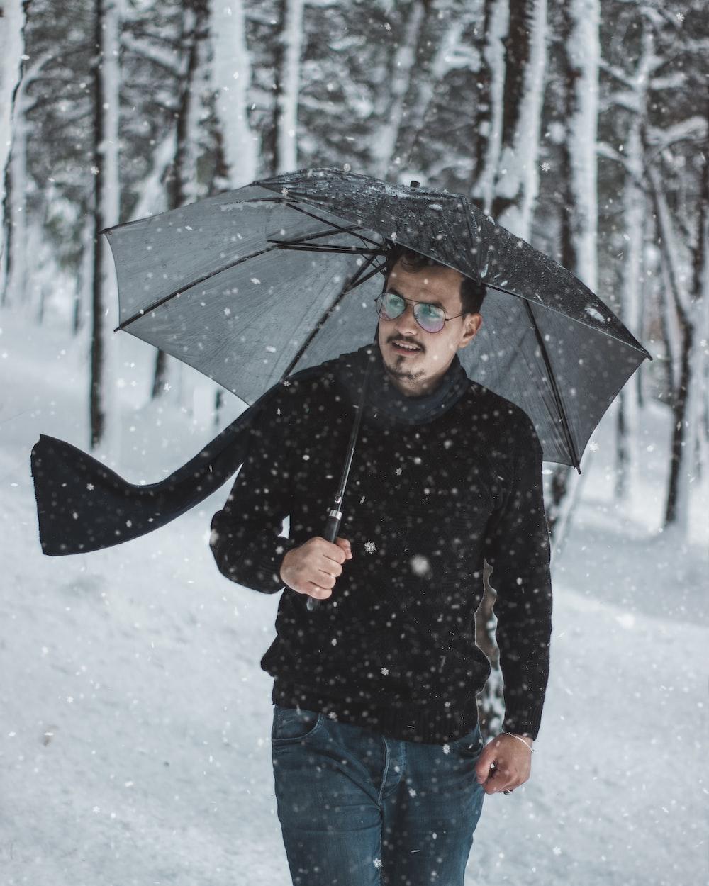 man holding umbrella outdoor during snowfall