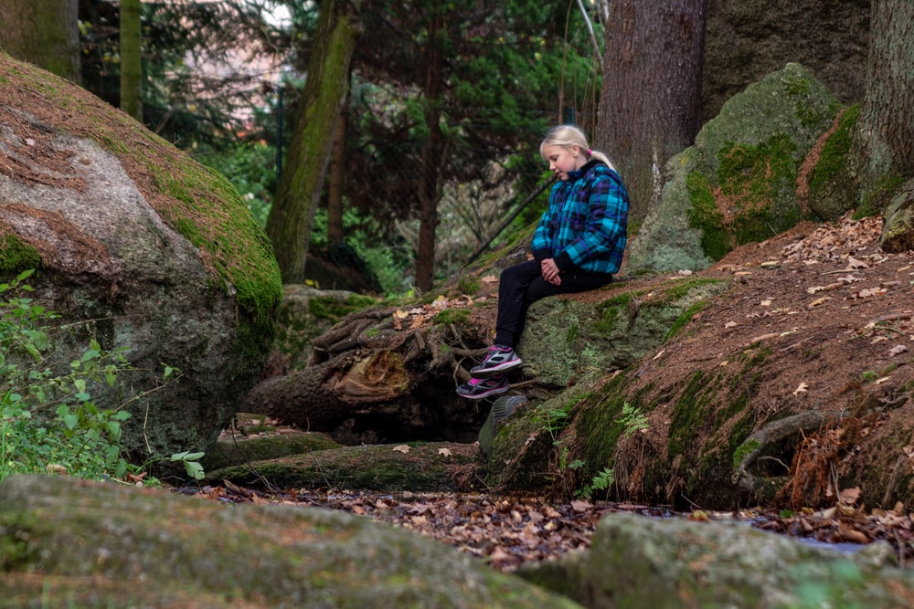 woman sitting on rock near trees