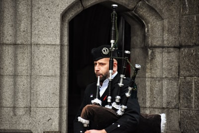 close-up photography of man playing musical instrument during daytime bagpipe teams background
