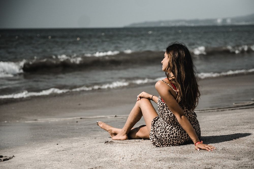 woman sitting on sand at beach