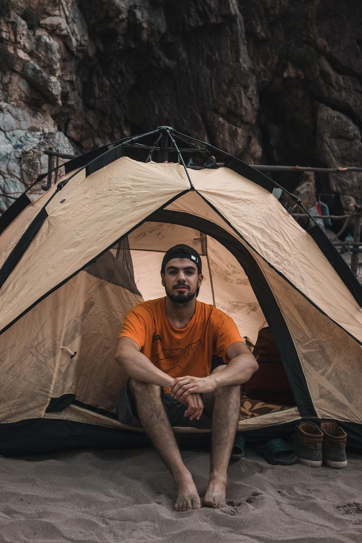 man sitting inside tent during daytime