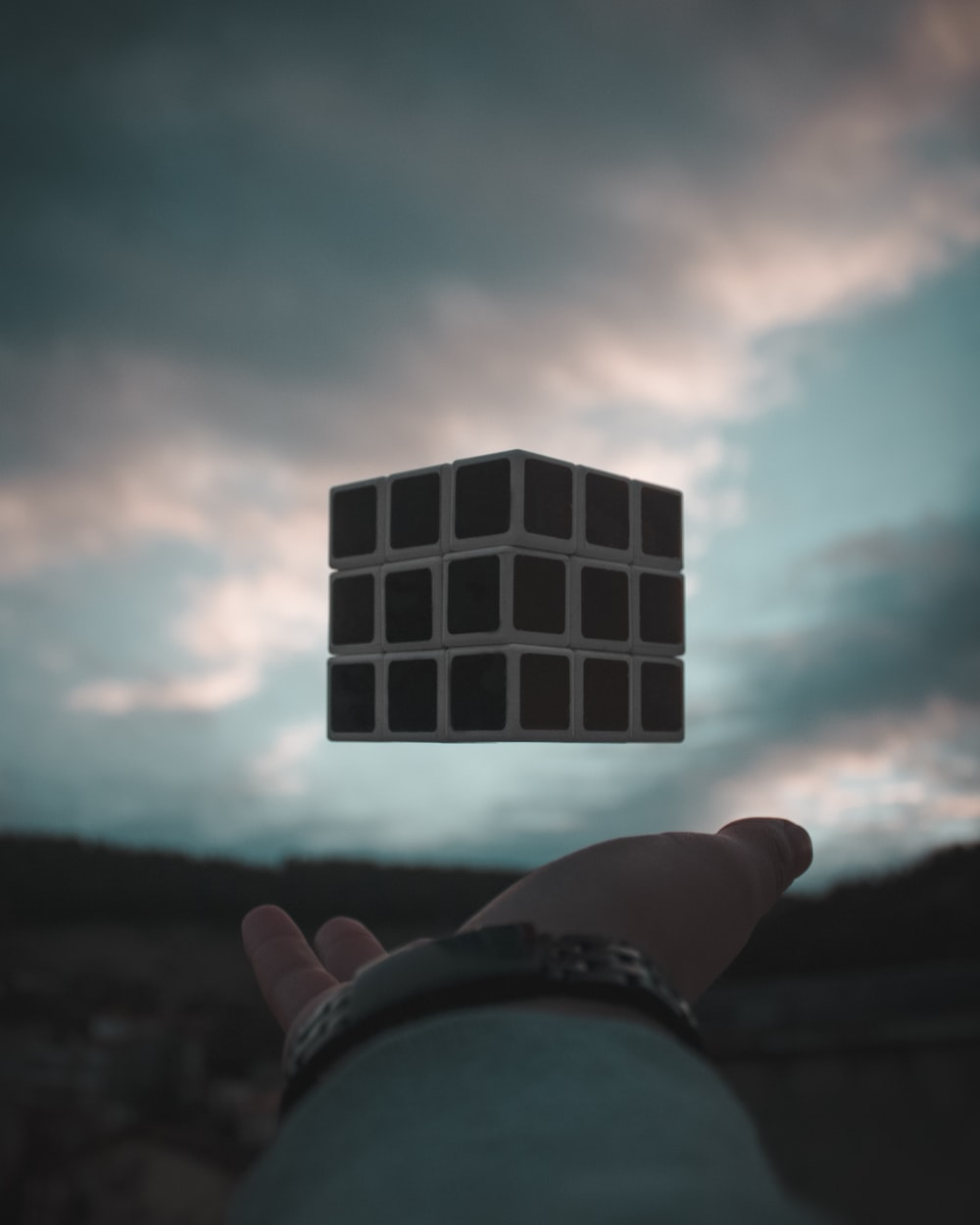 person tossing Rubik's cube