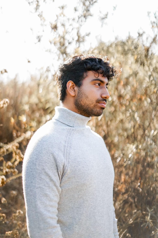 man standing beside dried plants