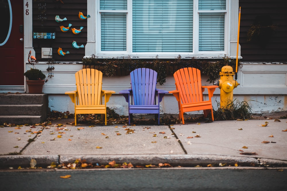 three Adirondack chairs with different colors outside a house