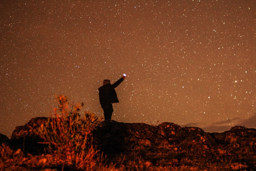 man standing on hill during nighttime