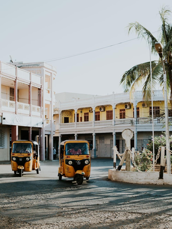 two yellow auto rickshaws near building during daytime