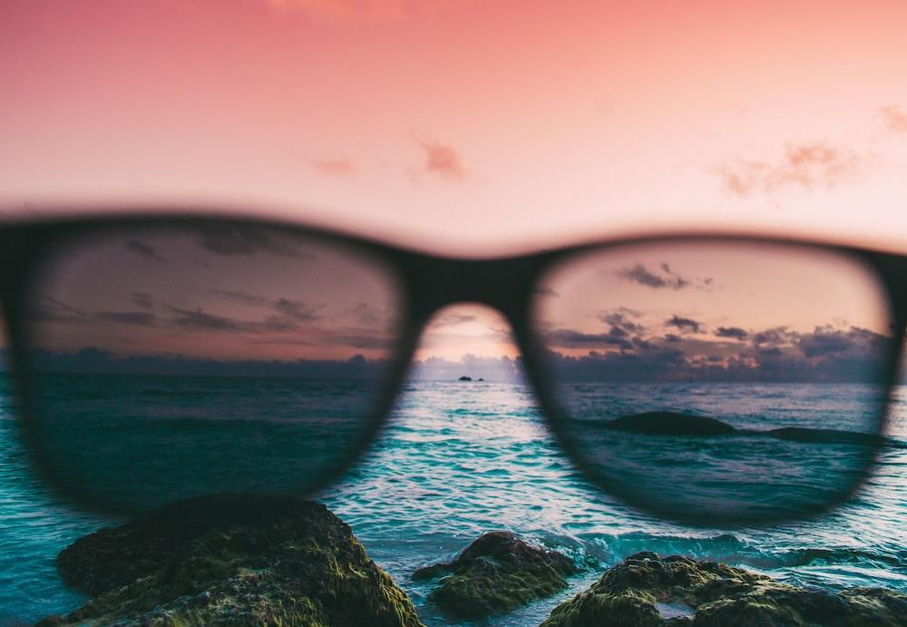 black Wayfarer-style sunglasses near body of water