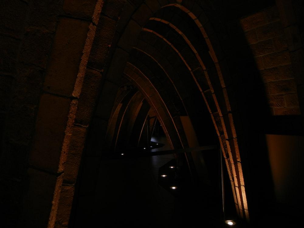 dim-lighted arch pathway