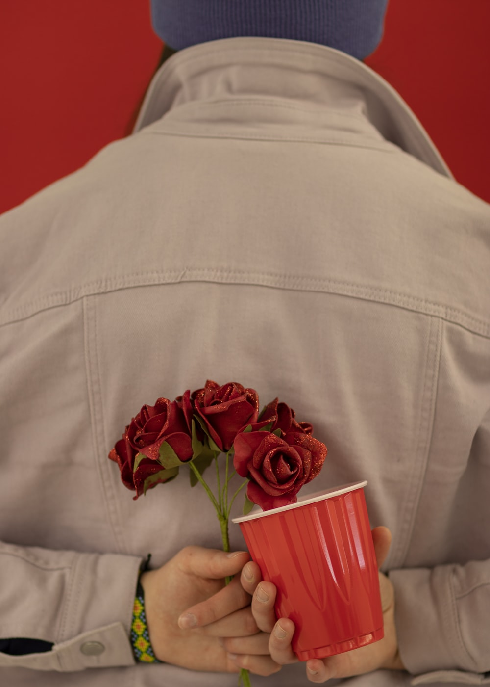 person holding red mug and red flowers