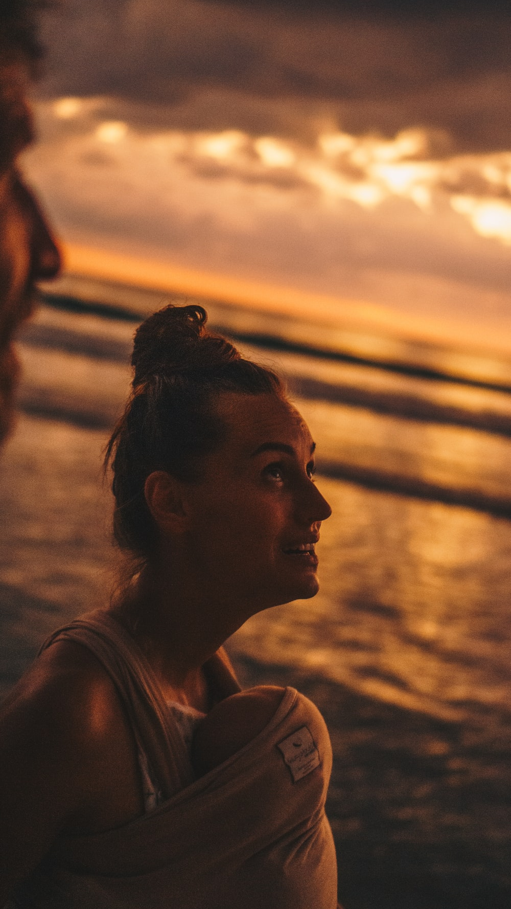woman looking upwards on shore during golden hour