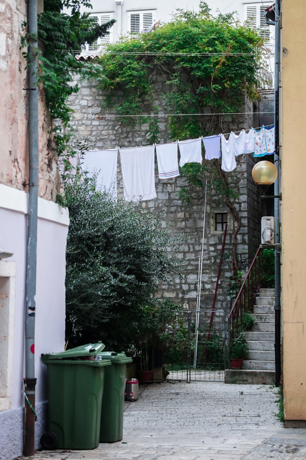 hung clothes near buildings and trash containers