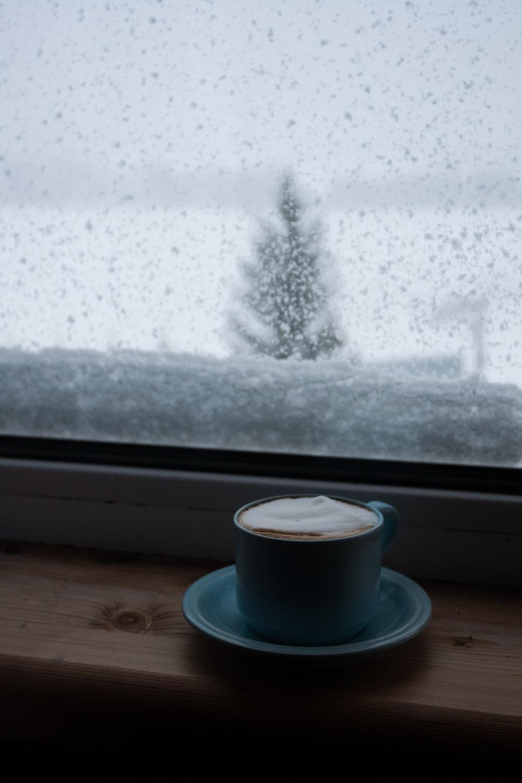 white ceramic coffee cup on saucer near window