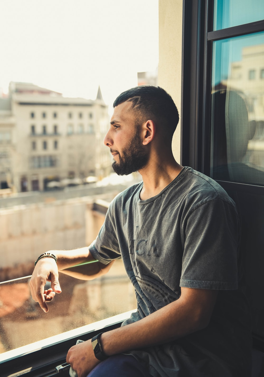 man in gray t-shirt by glass window
